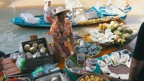 De Aziatische verkoper op kleine boot met vruchten en groenten verkoopt de goederen Pattaya het drijven markt stock footage