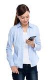 De Aziatische vrouw bekijkt mobiele telefoon Stock Fotografie