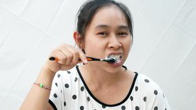 De Aziatische vrouw die enkel ontwaakte borstelde haar tanden met slaperigheid die zich over witte achtergrond bevinden stock video