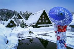 De Aziatische vrouw die Japanse traditionele kimono dragen bij shirakawa-gaat dorp in de winter, Unesco-de plaatsen van de wereld stock afbeeldingen