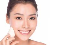 De Aziatische vrouw die van de make-upschoonheid stichtingsgezicht toepassen Royalty-vrije Stock Fotografie
