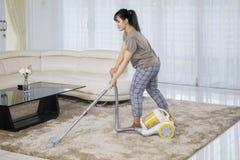 De Aziatische vrouw maakt tapijt met een stofzuiger schoon stock foto's