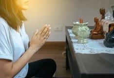 De Aziatische vrouw met dient het bidden Boedha standbeeldpositie in royalty-vrije stock foto's