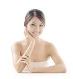 De Aziatische vrouw met skincare kijkt Stock Foto's