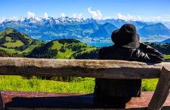 De Aziatische vrouw op de bank waardeert mooi toneelpanorama van majestueuze Zwitserse alpen dat omringend Rigi Kulm royalty-vrije stock afbeelding