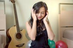 De Aziatische vrouw voelt gelukkige het luisteren muziek in hoofdtelefoons met kleurrijke ballons royalty-vrije stock afbeelding