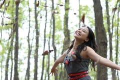De Aziatische vrouw werpt bladeren Stock Afbeelding