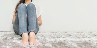 De Aziatische vrouw zit op grijze tapijtvloer met witte cement geweven achtergrond bij de hoek van huis met exemplaarruimte royalty-vrije stock foto's