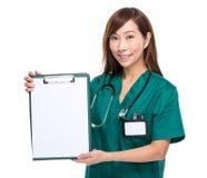 De Aziatische vrouwelijke arts toont klembord met leeg document Stock Foto's