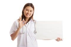 De Aziatische vrouwelijke arts toont O.K. teken met leeg teken Stock Foto