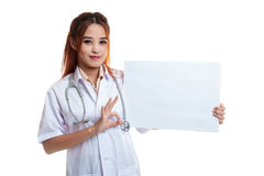 De Aziatische vrouwelijke arts toont O.K. teken met leeg teken Royalty-vrije Stock Foto