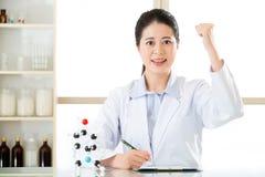 De Aziatische vrouwelijke wetenschapper succesvolle ontdekking berekent Chemisch product stock fotografie