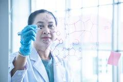 De Aziatische vrouwen chemische wetenschapper schrijft formule op glasraad royalty-vrije stock foto