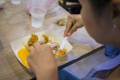 De Aziatische vrouwen die gebraden kip, de handgreep gebraden kip van de nadrukvrouw eten voor eten, meisje met snel voedselconce stock afbeeldingen