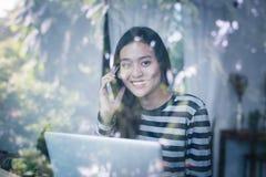 De Aziatische vrouwen gebruiken gelukkig een telefoon Stock Afbeelding