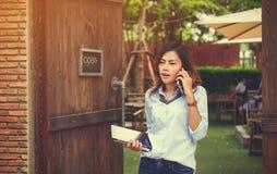 De Aziatische vrouwen gebruiken hun mobiele telefoons stock afbeelding