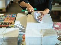 De Aziatische vrouwen vouwen een stuk van document aan klaar om boeken te maken Royalty-vrije Stock Foto