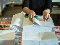 De Aziatische vrouwen vouwen een stuk van document aan klaar om boeken te maken Stock Afbeeldingen