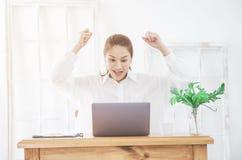 De Aziatische vrouwen werken met grijze laptops aan de bank in de ruimte in de ochtend stock foto