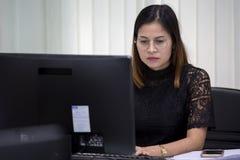De Aziatische vrouwen in zwarte kleding gebruiken computers aan het bedrijfswerk bij haar stock foto