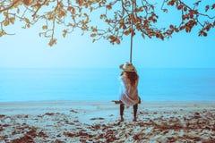 De Aziatische vrouwenreis ontspant in de vakantie Zit op een schommeling bij het strand stock afbeelding