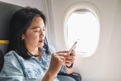 De Aziatische Vrouwenzitting bij vensterzetel in vliegtuig en zet airpl aan Stock Afbeelding