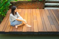 De Aziatische vrouwenzitting ontspant op houten terras of portiek dichtbij vijver in de tuin stock foto's