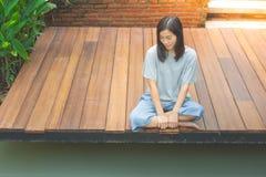 De Aziatische vrouwenzitting ontspant op houten terras of portiek dichtbij vijver in de tuin stock afbeeldingen