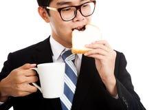 De Aziatische zakenman eet brood en koffie als ontbijt Royalty-vrije Stock Afbeeldingen