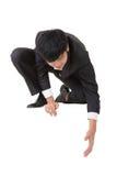 De Aziatische zakenman gaat zitten en buigt om somebody te helpen Stock Afbeeldingen