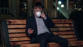 De Aziatische zakenman in het nachtpark gebruikt een smartphone en het drinken van een kop van koffie stock video