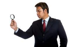 De Aziatische zakenman kijkt door een vergrootglas Stock Foto's