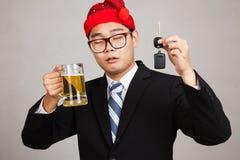 De Aziatische zakenman met partijhoed, drinkt bier, krijgt dronken, greepauto Royalty-vrije Stock Fotografie