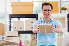 De Aziatische zakenman in toevallig overhemd was inpakt pakketten, workin royalty-vrije stock foto's