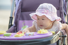 De Aziatische zitting van het babymeisje en het spelen in wandelwagen op een gang Royalty-vrije Stock Afbeeldingen