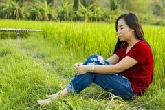 De Aziatische zitting van het tienermeisje in en padieveld die gelukkig herinnerd aan verleden groot verhaal denken glimlachen royalty-vrije stock afbeelding