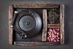 De Aziatische zwarte traditionele theepot met droge thee en nam in uitstekende houten doos toe Stock Afbeelding