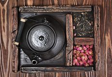 De Aziatische zwarte traditionele theepot met droge thee en nam in uitstekende houten doos toe Royalty-vrije Stock Fotografie