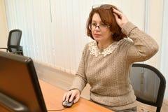 De bärande anblickarna för kvinnan ser i datorbildskärmen som rymmer de andra exponeringsglasen på huvudet Royaltyfri Bild