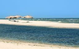 De baai en het strand van de open zee met een strand en met stro bedekte paraplu's met zonbedden, Royalty-vrije Stock Afbeeldingen