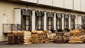 De baaien van de pakhuisvrachtwagen met gestapelde houten pallets stock afbeeldingen