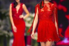 De baan van de manierloopbrug toont modellen rode kleding stock foto's