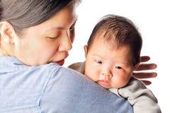 De baby baseert zich op het wapen van de moeder Stock Foto
