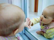 De baby bestudeert zich in de spiegel royalty-vrije stock foto's