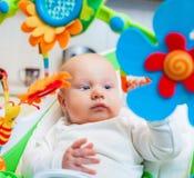 De baby clutched kleurrijk stuk speelgoed Stock Afbeeldingen