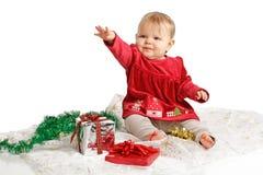 De baby in de rode kleding van fluweelKerstmis bereikt omhoog Stock Foto