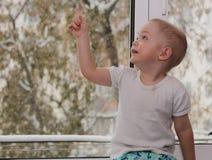 De baby dichtbij het venster, jongen Stock Foto's