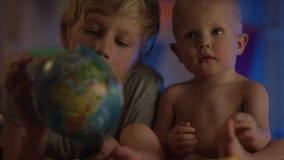 De baby die van Nice enkel bij slecht zitten en met bol en zijn broer spelen maakt bedrijf stock video