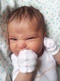 De baby die zijn vuist bijten en maakt een gezicht Stock Foto's