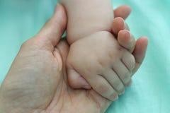 De baby dient de hand van de brij in Stock Afbeelding